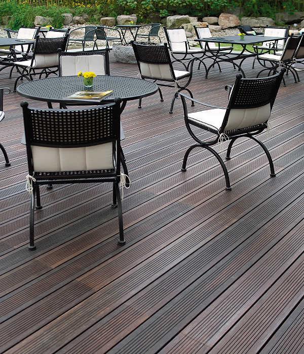 Große Terrassse mit Garten und dunklen Bambus Terrassendielen und mehreren Sitzgruppen.