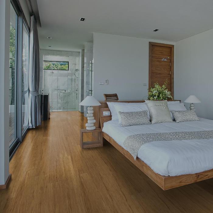 Helles Schlafzimmer mit großem Bett und Bambus Parkett in natur braun. Bodentiefe Fenster links.