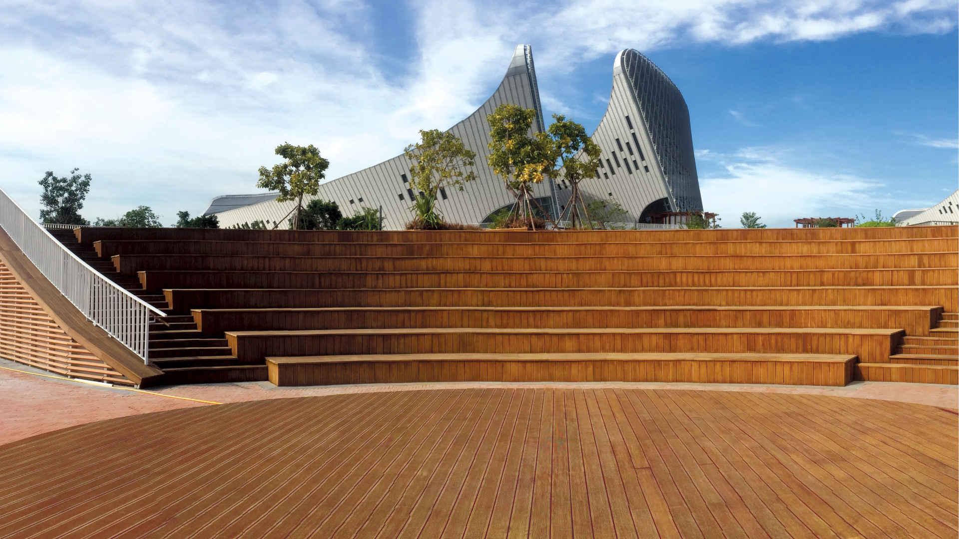 Große Sommerbühne aus hellbraunen Bambus Terrassendielen mit Konferenzzenter im Hintergrund